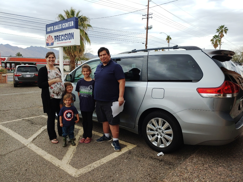 Happy family with their new Toyota Sienna