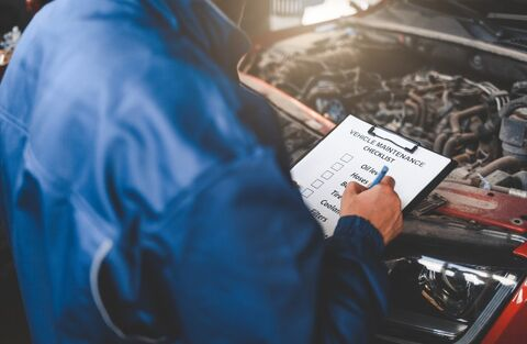 Man completing a vehicle inspection with a list