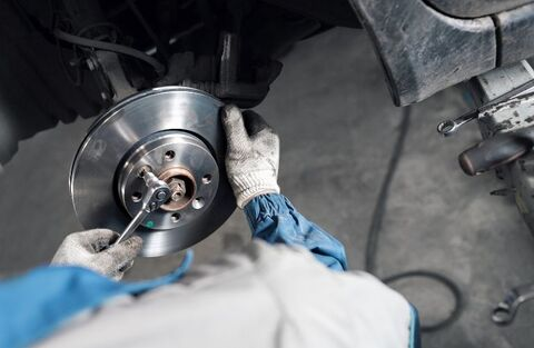 Mechanic with Rubber Gloves Working on Brakes